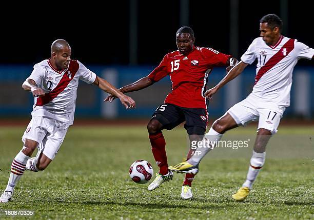 Trinidad & Tobago's Kevon Carter vies for the ball with Peruvians Alberto Rodriguez and Carlos Lobaton during their friendly match at Ato Bolton...