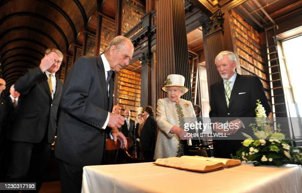 Trinity College provost John Hegarty looks on while Britain's Queen Elizabeth II and Prince Philip , Duke of Edinburgh, sign the guest book in the...