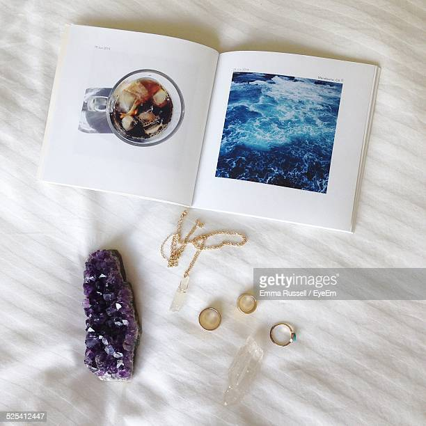 Trinkets And Open Booklet On White Cloth