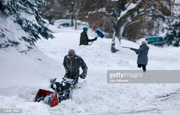 A trio digs out of the Green Mountain neighborhood on November 26 2019 in Lakewood Colorado A blizzard warning was issued to residents for the...
