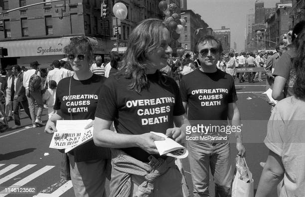A trio of activists all in tshirts that read 'Overeating Causes Death' hand out pamphlets on 9th Avenue during the International Food Festival in...