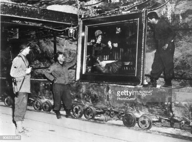 A trio of American soldiers from the Third United States Army examine Edouard Manet's 'Wintergarden' in the Merkers salt mine where it had been...