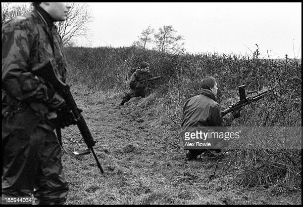 A trio of British soldiers cautiously peer through a hedgerow during a patrol in County Fermanagh along the border separating Northern Ireland and...