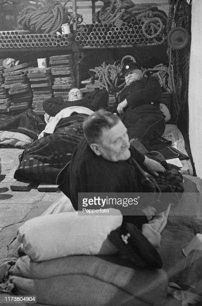 A trio of Chelsea Pensioners bed down in a storeroom designated as an air raid shelter at the Royal Hospital Chelsea during a German air raid over...