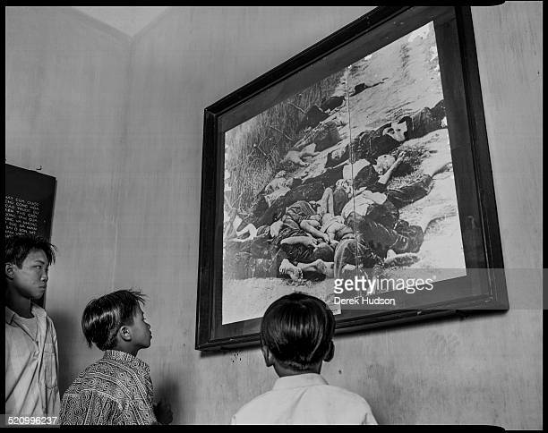 Trio of children look at a photograph of the My Lai massacre in an unidentified war museum, Ho Chi Minh City, Vietnam, 1995. During the massacre,...