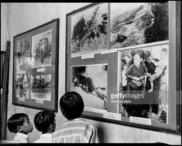 Trio of children look at photographs of the My Lai massacre in an unidentified war museum, Ho Chi Minh City, Vietnam, 1995. During the massacre,...