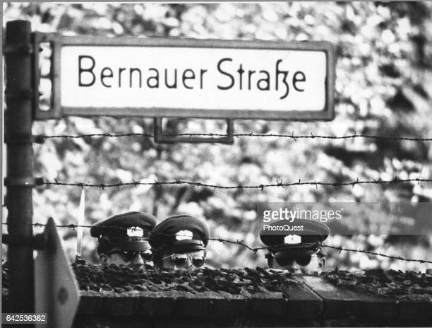 A trio of East German policemen all in caps and sunglasses peer over a section of the Berlin Wall Berlin Germany 1961 They on the opposite side of...