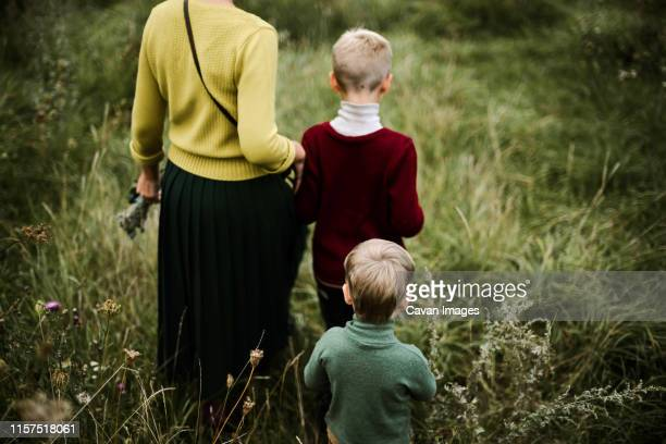 a trio of family walking from behind  in the meadow - legs behind head stock pictures, royalty-free photos & images