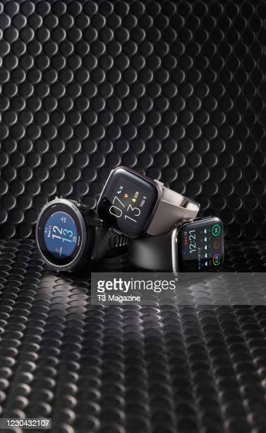 Trio of fitness smartwatches, including a Garmin Forerunner 945, Fitbit Versa 2 and Apple Watch Series 5, taken on March 11, 2020.