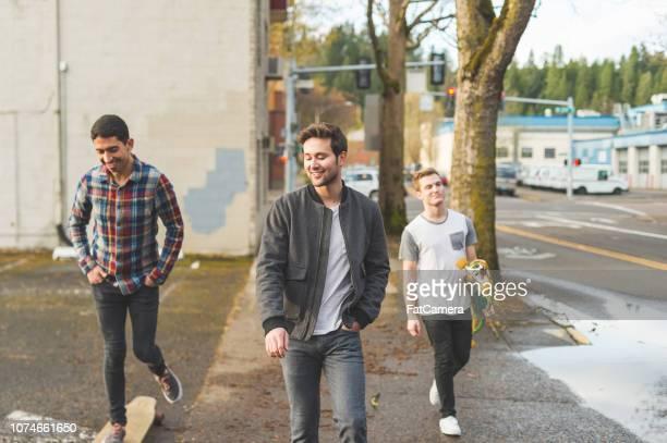 Trio of friends longboard through city