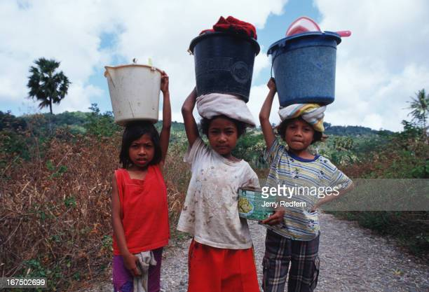 A trio of friends pose for a portrait on the trail leading to the town's water supply where they will do their families' laundry