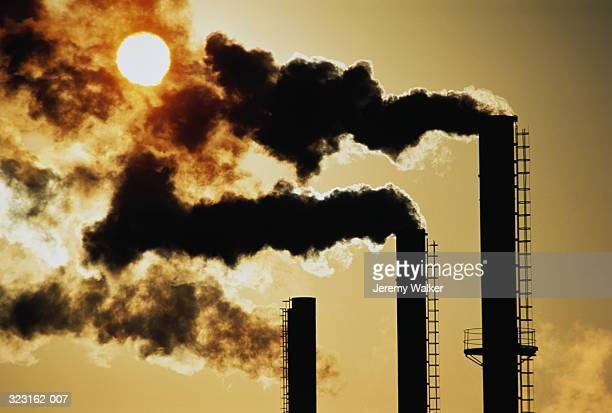 trio of industrial chimneys emitting smoke,sunset,silhouette - air pollution stock pictures, royalty-free photos & images