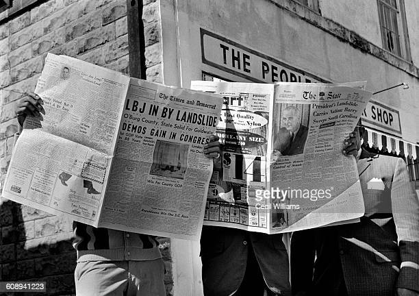 A trio of men read opened copies of the newspapers that announce in their headlines President Lyndon Johnson's landslide reelection victory are...