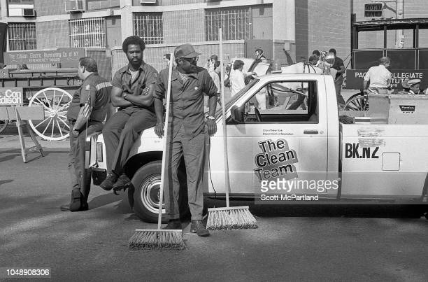 A trio of sanitation workers take a break as they sit or lean on a 'Clean Team' pickup truck during the Brooklyn Bridge's 100th birthday celebrations...