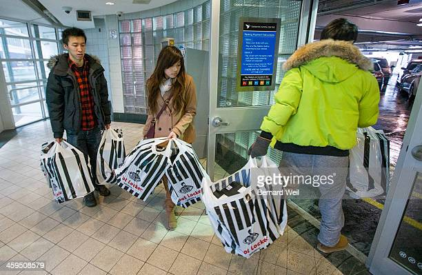 TORONTO ON DECEMBER 26 A trio of shoppers leaves Eaton Centre into the parking lot loaded with ichael Jordan running shoes during Boxing Day They...