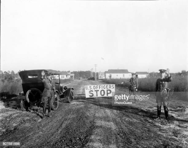 A trio of uniformed officers block a road with outstretched hands and a sign that reads 'US Officers Stop' Gainesville Florida 1926