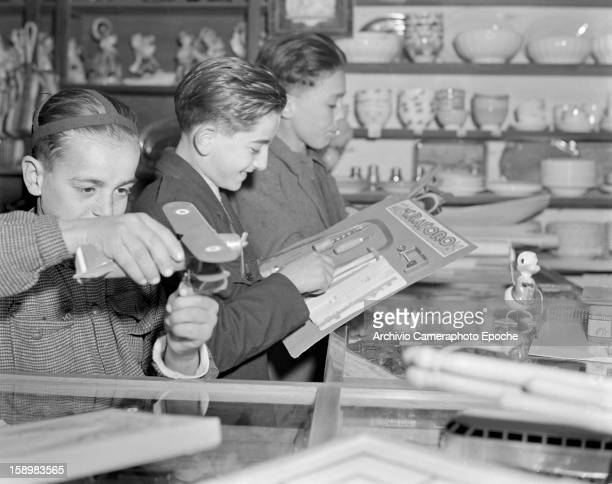 A trio of young boys play with the merchandise in a toy shop Trieste Italy 1950