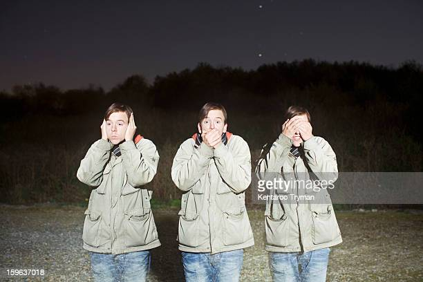 Triple exposure of a young man in hear no evil, see no evil, speak no evil poses