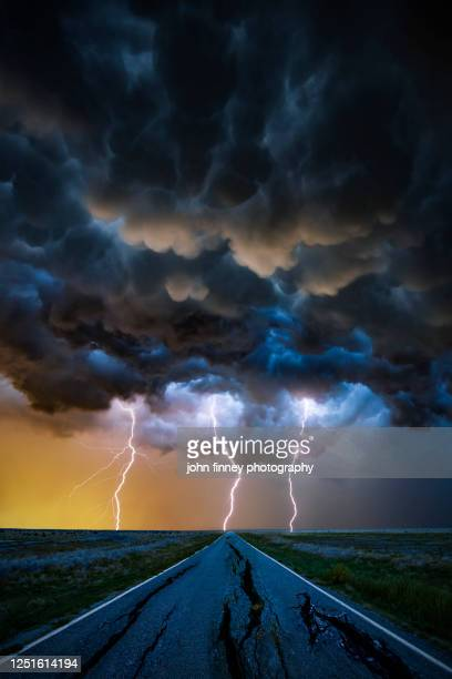 triple lightning bolts with a broken road vanishing into the distance - dramatic sky stock pictures, royalty-free photos & images