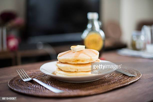 Triple pancakes with butter and maple syrup.