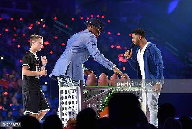 $50K Triple Shot contestant Jake Lombardo NFL player Cam Newton and host Russell Wilson participate in a contest onstage during the Nickelodeon Kids'...