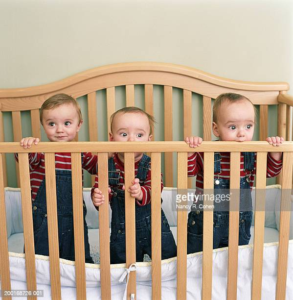 Triplet baby boys (9-12 months) standing in crib