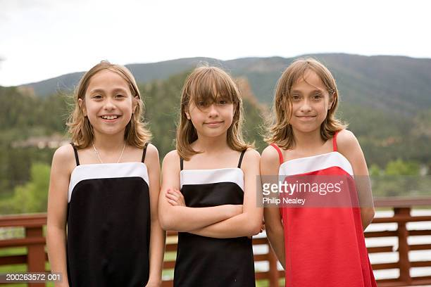 Triplet girls (8-10), smiling, portrait