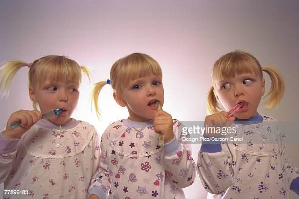 Triplets brushing teeth