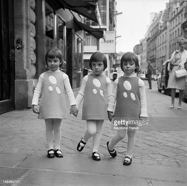 Triplets displays a creation of French Designer Pierre Cardin for his children collection in the Faubourg St Honore on April 18 1968 in Paris France