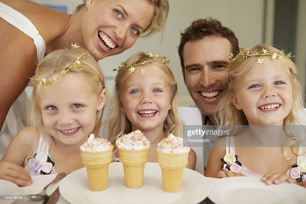 Triplets having ice cream, parents in background : Stock Photo