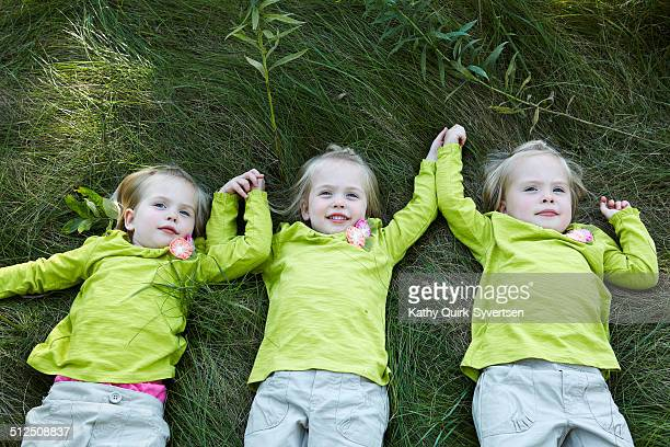 Triplets holding hands in tall grass field