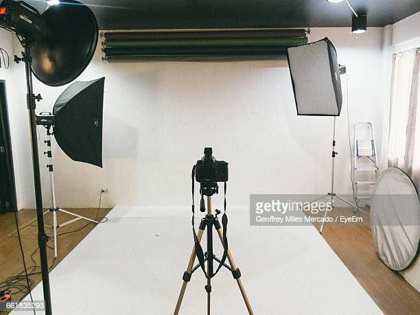 tripod camera and lighting equipment in empty studio - film studio stock pictures, royalty-free photos & images
