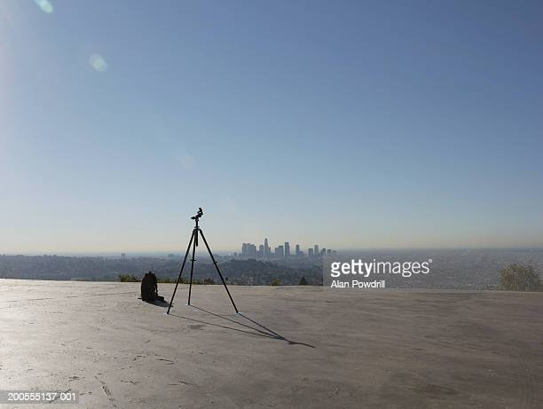 Tripod stand set on rooftop against city skyline