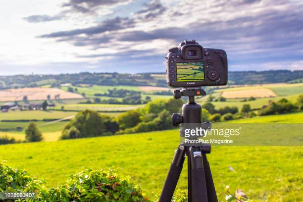 Tripod-mounted Canon DSLR camera taking pictures of the British countryside, taken on July 29, 2019.