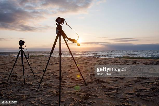 Tripods and cameras on the beach at sunset