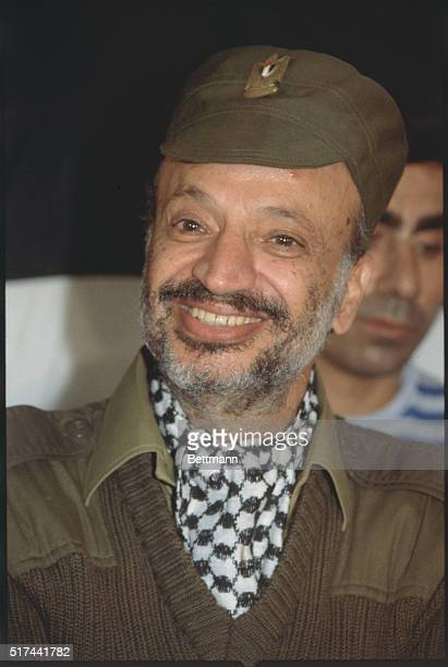 PLO Leader Yassar Arafat smiles during a press conference at PLO headquarters He is wearing an olivedrab hat and a black and white check scarf