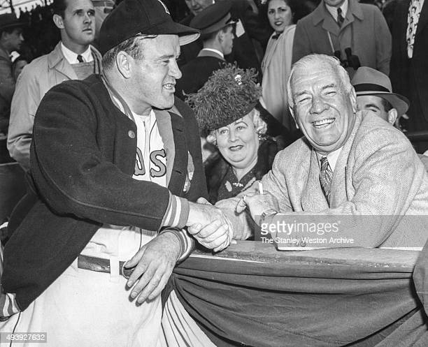 Tris Speaker wishes good luck to manager Joe Cronin of the Boston Red Sox before Game 3 of the 1946 World Series against the St. Louis Cardinals at...