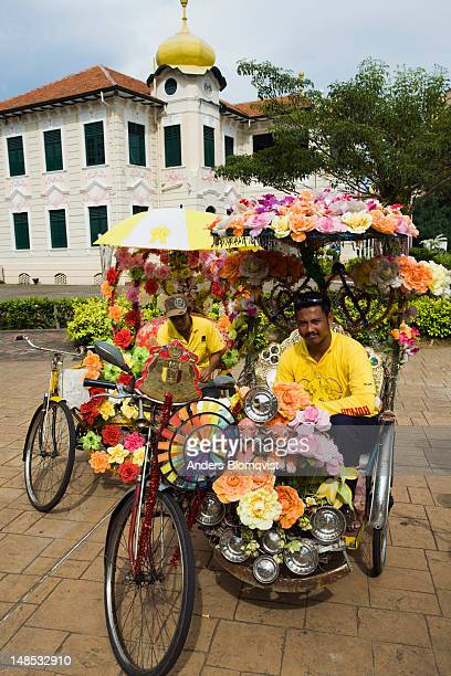 Trishaw drivers with their flower decorated trishaws by Proclamation of Independence Memorial.