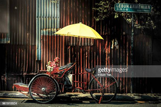 trishaw with yellow umbrella at the back street in penang - george town penang stock photos and pictures