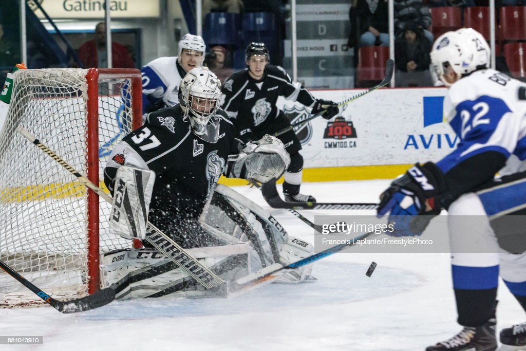 Tristan Berube #37 of the Gatineau Olympiques makes a save as Anthony Boucher #22 of the Saint John Sea Dogs looks for the rebound on December 1, 2017 at Robert Guertin Arena in Gatineau, Quebec, Canada.