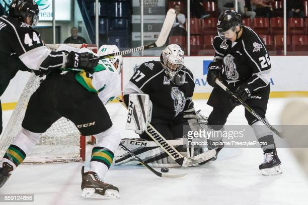 Tristan Berube of the Gatineau Olympiques makes a save as Mitchell Balmas and Gabriel Bilodeau defend against Adam Cheezo of the Vald'Or Foreurs at...