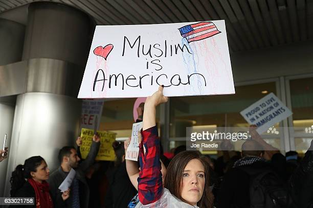 Tristan Houghton joins with other protesters as they stand together at the Miami International Airport against the executive order that President...