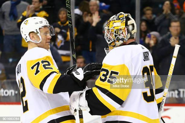 Tristan Jarry and Patric Hornqvist of the Pittsburgh Penguins celebrate a 40 win against the New York Islanders at Barclays Center on January 5 2018...