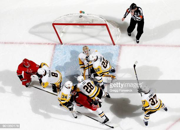 Tristan Jarry of the Pittsburgh Penguins lays down on a loose puck in the crease as teammates Matt Hunwick Ian Cole Tom Kuhnhackl Carter Rowney and...