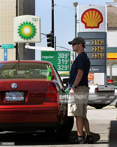 Tristan Jenista pumps gas at a BP Amoco gas station with high gas prices near a Shell station with even higher prices August 29, 2005 in Chicago,...