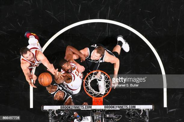 Tristan Thompson and Kevin Love of the Cleveland Cavaliers and Rondae HollisJefferson of the Brooklyn Nets jump for the rebound on October 25 2017 at...