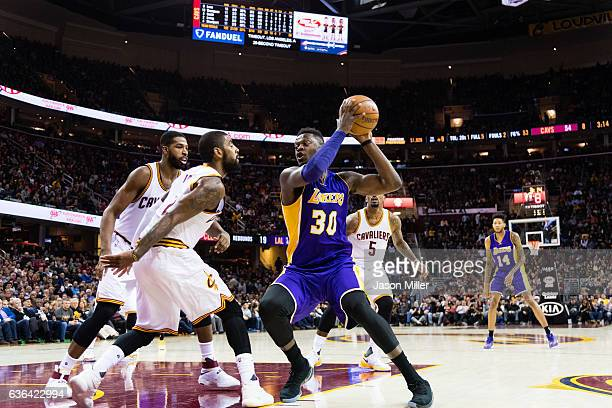 Tristan Thompson and Kyrie Irving of the Cleveland Cavaliers guard Julius Randle of the Los Angeles Lakers during the first half at Quicken Loans...