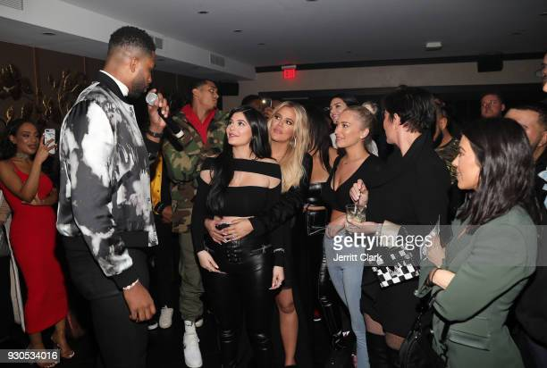 Tristan Thompson blows out his birthday candles as Khloe Kardashian Kylie Jenner Kris Jenner Kourtney Kardashian and friends look on at Remy Martin...