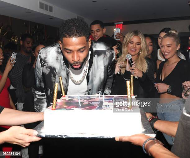 Tristan Thompson blows out his birthday candles as Khloe Kardashian and friends look on at Remy Martin Presents Tristan Thompson's Birthday at Beauty...