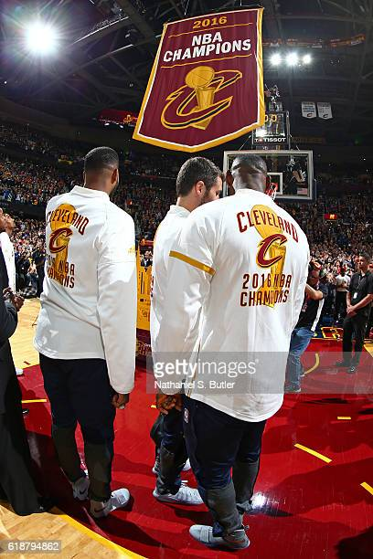 Tristan Thompson, Kevin Love and LeBron James of the Cleveland Cavaliers stand on the court as the championship banner is raised before the game...